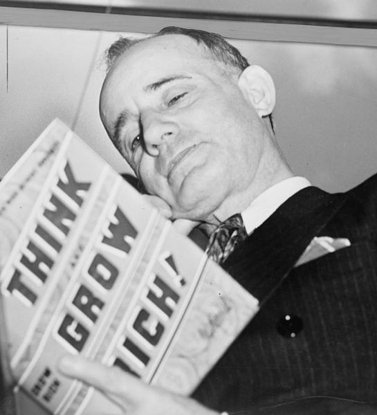 Napoleon Hill holding a copy of his book Think and Grow Rich
